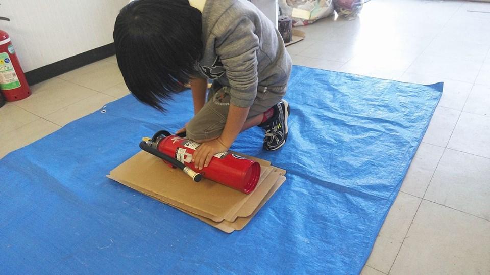 消火器の解体をする小学生
