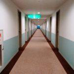 ホテルの廊下で左右対称の規律を乱す消防設備